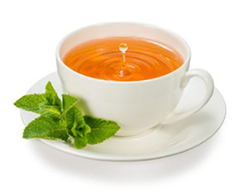 Чашка успокоительного чая, рядом лежат листочки мелиссы