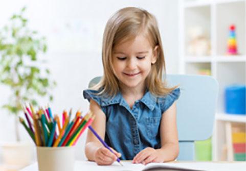 Девочка ровно сидит за столом и рисует карандашами