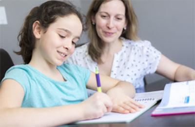 Мама смотрит за тем, как дочка пишет