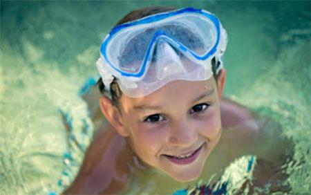 Мальчик в бассейне. На голове маска для подводного плавания