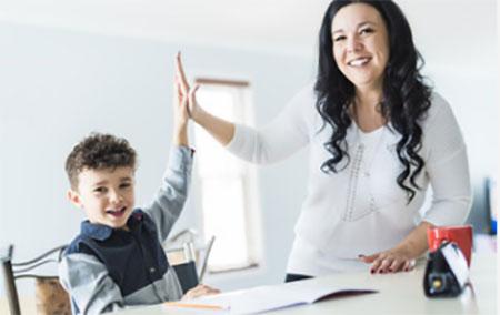 Мама хлопает одной рукой в ладош своего сына. Оба рады. Ребенок сидит за столом, перед ним открытая тетрадь