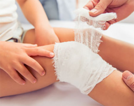 Ребенку забинтовывают колено