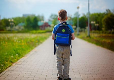 Идущий по тропинке мальчик с рюкзаком на плечах