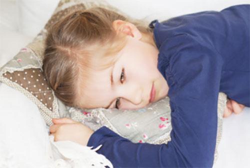 Девочка лежит на подушке. Она явно плохо себя чувствует