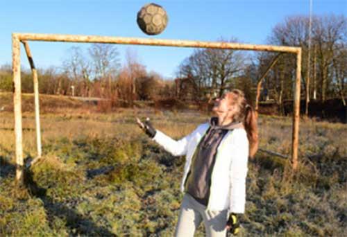 Девочка с мячом возле футбольных ворот