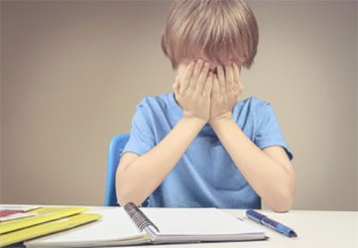 Расстроенный мальчик с закрытым лицом, рядом лежит открытая тетрадь