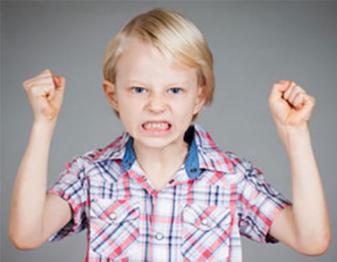 Мальчик замахивается двумя руками, хочет ударить