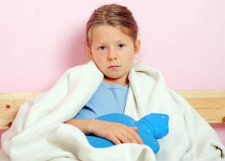 Замерзшая девочка укуталась в одеяло, держит грелку