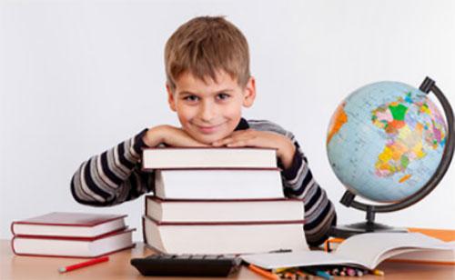 Перед довольным мальчиком книги, рядом стоит глобус