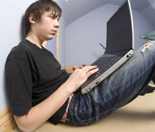 Тринадцатилетний мальчик сидит на полу и играет на ноутбуке