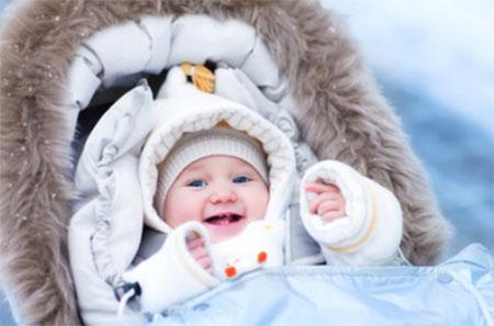 Грудной ребенок одетый по погоде в теплой коляске зимой