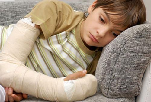 Грустный мальчик с загипсованной рукой лежит на диване