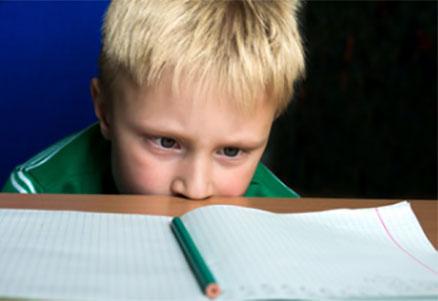 Грустный ребенок перед открытой тетрадью
