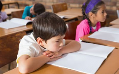Ученики сидят за партами с открытыми тетрадками и слушают.