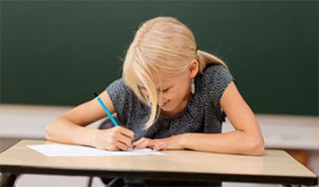 Девочка сидит за партой и увлеченно пишет в тетради