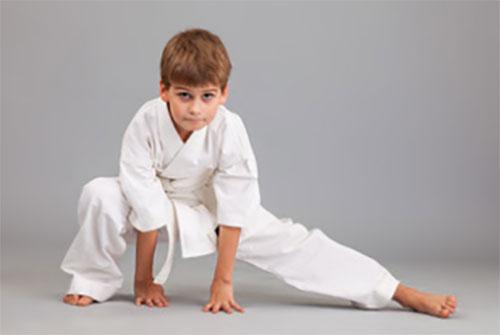 Мальчик, занимающийся боевыми искусствами, стоит в стойке