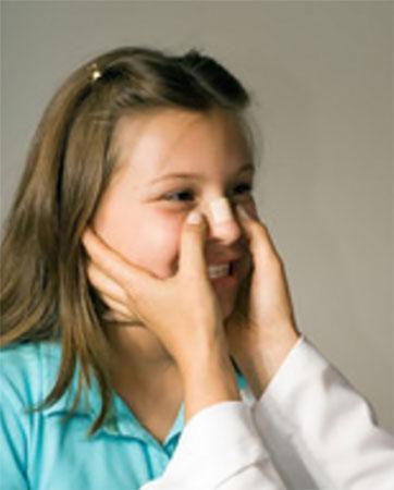 Девочке на нос накладывают лейкопластырную повязку