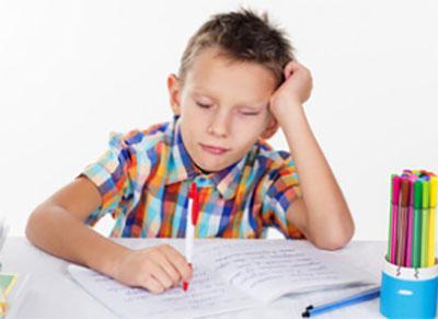 Мальчик нехотя пишет в тетради