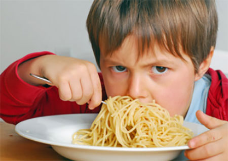 Ребенок ест большую порцию макарон