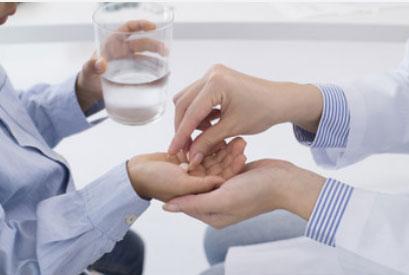 Ребенок держит стакан с водой. Ему в руку кладут таблетку