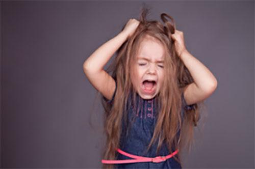 Девочка пытается вырвать себе волосы в приступе истерики