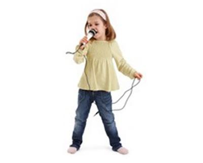 Девочка поет. В руках держит микрофон