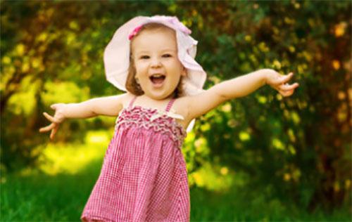 Радостная девочка в панамке и легком платьице