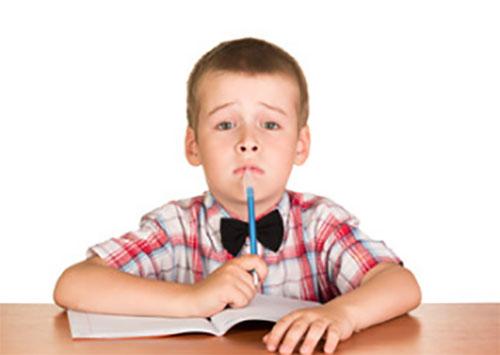 Мальчик задумался над написанием сочинения