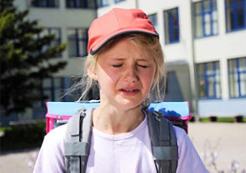 Плачущая девочка с рюкзаком на плечах