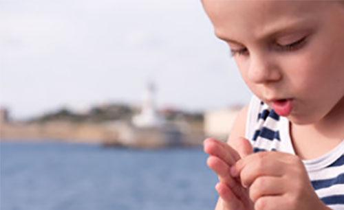Мальчик рассматривает занозу на пальце руки
