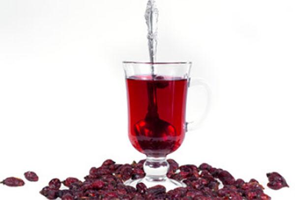 Отвар шиповника в бокале и сушенные ягоды