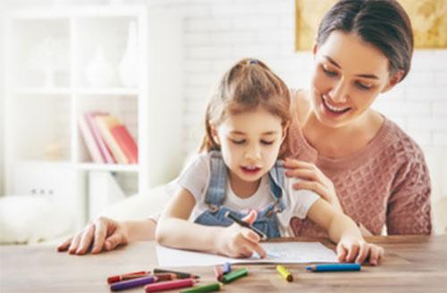 Мама смотрит, как дочка рисует