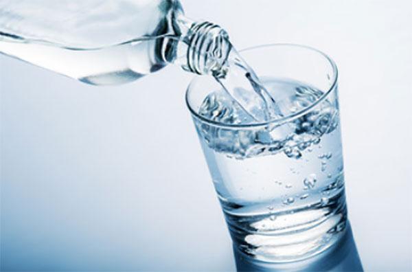 С бутылки наливают воду в стакан