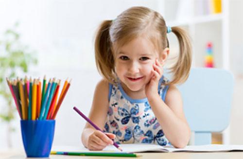 Девочка рисует и улыбается