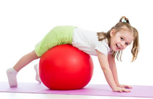 Девочка занимается на фитболе