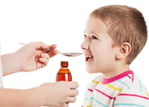 Мальчику дают лекарство в виде сиропа