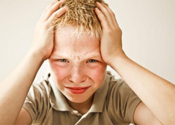 Мальчик держится за голову двумя руками, ему больно