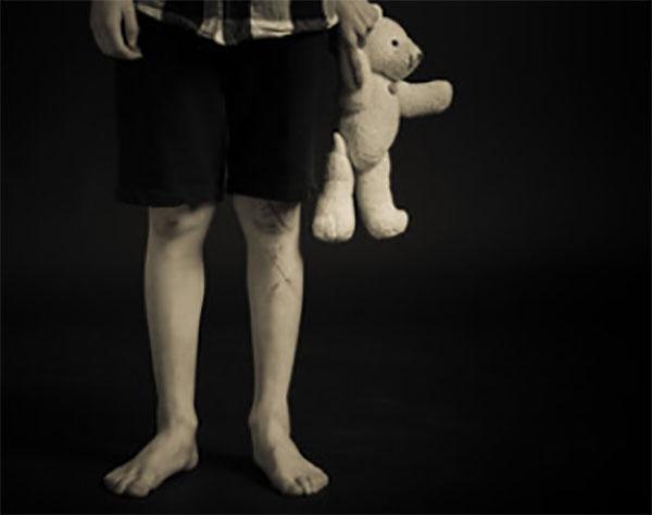 Ноги мальчика с игрушкой в руках. Стоит в темноте