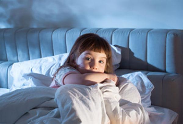 Испуганная девочка в постели