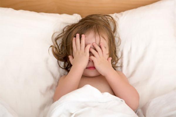 Ребенок лежит в постели, закрывает лицо руками