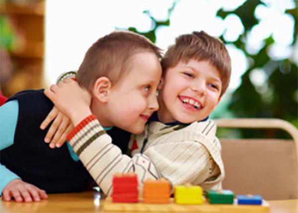 Мальчик на радостях обнимает другого. Перед ними простая детская игра на собирание предметов одинакового цвета
