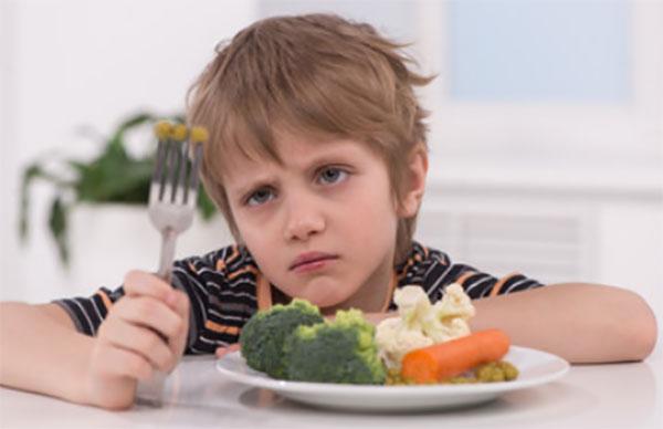Печальный и бледный ребенок сидит перед тарелкой с овощами