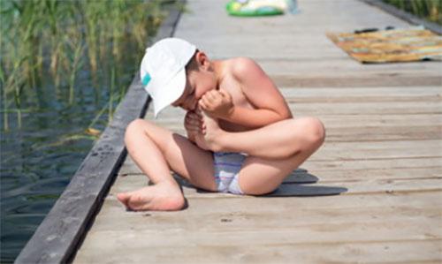 Мальчик сидит на причале из досок и пытается отсосать занозы, проникшую в его стопу