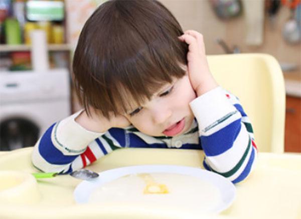 Ребенок не хочет есть, сидит перед тарелкой с едой