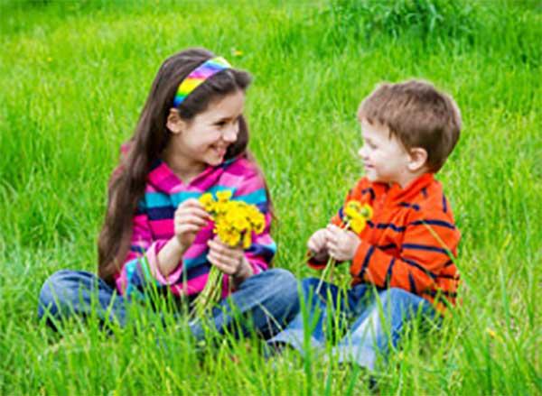Девочка и мальчик помладше сидят на траве с цветами в руках и разговаривают