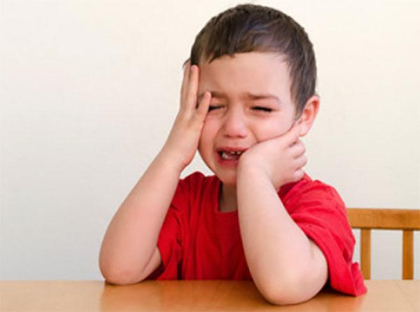 Мальчик сидит за столом и плачет