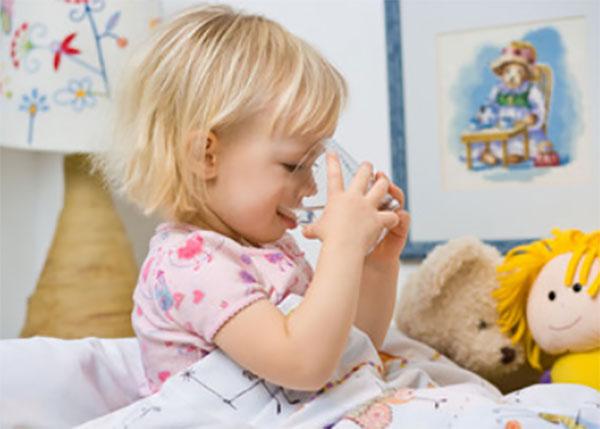 Девочка сидит в кровати и пьет воду