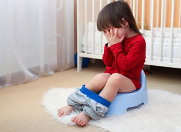 Ребенок сидит на горшочке и прячет ручками свое лицо
