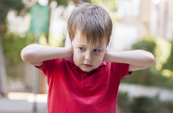Мальчик закрывает уши руками