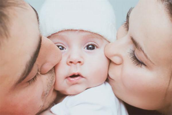 Мама и папа с двух сторон целуют щечки крохотного сыночка